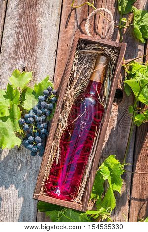 Rose wine in a wooden box on old wooden table