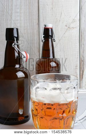 Two swing top beer bottles in a rustic bar setting with a half drunk frosty mug in the foreground. Horizontal format with copy space.