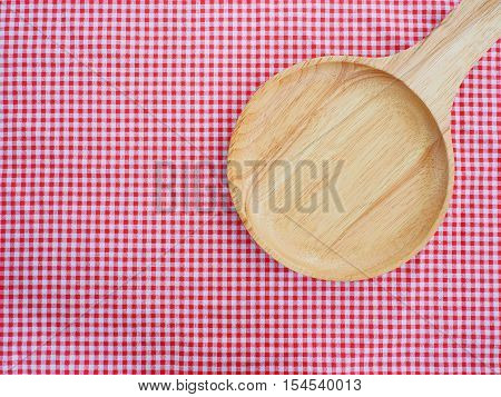 Empty plate and spoons on red checked tablecloth with copy space. Top view.