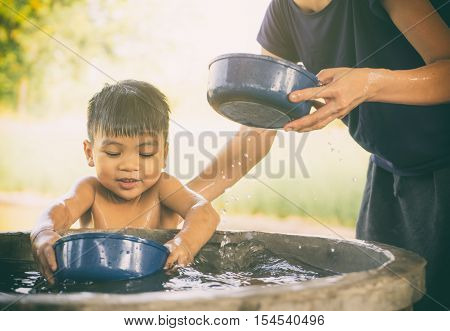 Mother is taking a bath for her son in country water well.