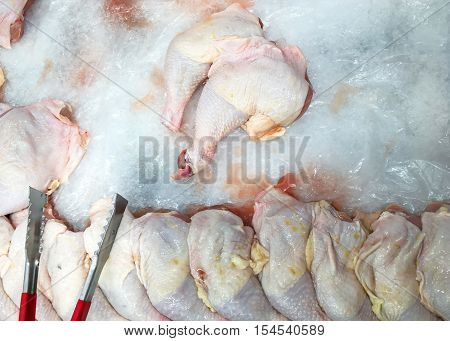 Fresh raw chicken on sale in retail display. Lot of raw chicken legs are put on ice to keep it freshness. Raw chicken meat are freeze for customer choice in supermarket.