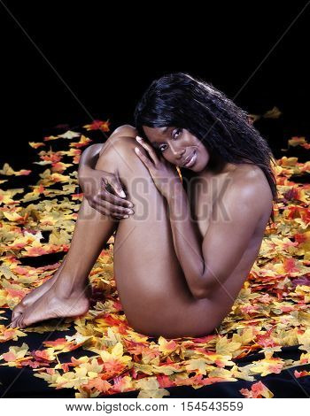 Implied Nude African American Woman Sitting Among Silk Autumn Leaves On Dark Background