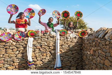 Axum Ethiopia - January 20 2016: Joung craft vendors between the ruins of the baths of the Queen of Saba