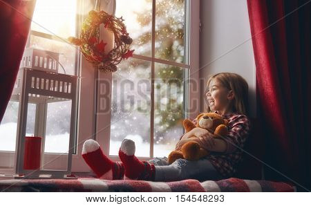Merry Christmas and happy holidays! Cute little girl with toy teddy bear sitting by the window and looking at the winter forest. Room decorated on Christmas. Kid enjoys the snowfall.