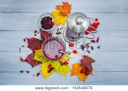 Still Life Cup Of Fruit Tea And Kettle On Autumn Leaves And Vintage Wood Background.