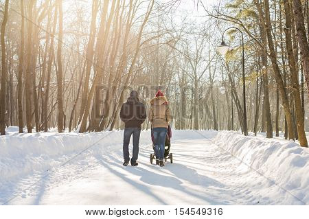 Happy young family walking in the park in winter. The parents carry the baby in a stroller through the snow