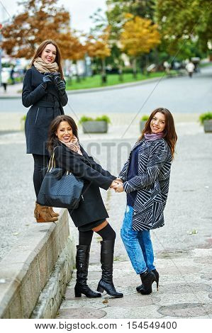 Three young attractive girls having fun taking pictures together on city walk . A way of life .