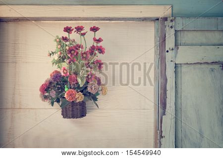 Artificial flowers on wood wall , in vintage style