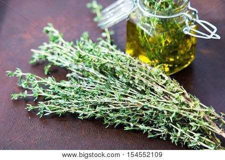 Thyme Oil. Thyme Essential Oil Jar Glass Bottle And Branches Of Plant Thyme With Flowers On Rustic B