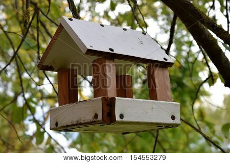 White birdfeeder nesting box hanging on the tree.