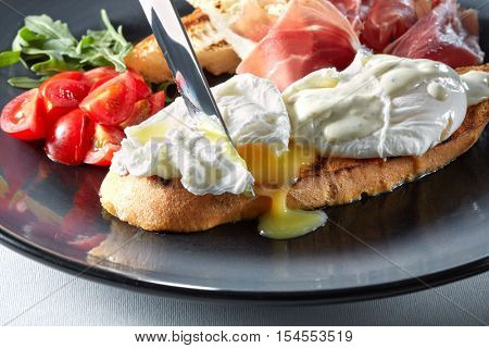 The knife cuts the Eggs Benedict on toasted bread with ham, tomatoes and sauce