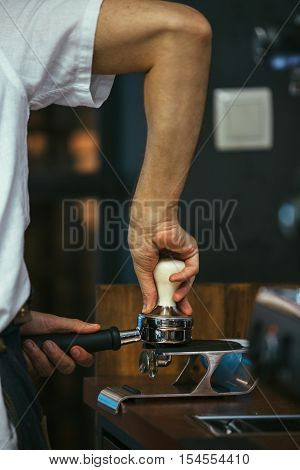 Close-up of bartender using tamper to press ground coffee into porta filter