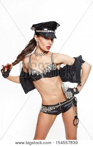 sexy beautiful brunette semi nude police woman with long curly hair with handcuffs and glasses with birght makeup and red lips isolated on white