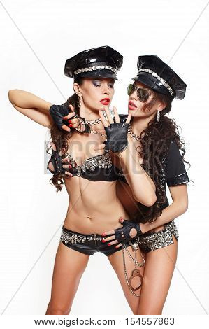 two sexy beautiful brunette semi nude police women with long curly hair with handcuffs with glasses with birght makeup and red lips one girl arresting another