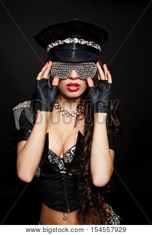 sexy beautiful brunette semi nude police woman with long curly hair with handcuffs with birght makeup and red lips isolated on black in fashion glasses