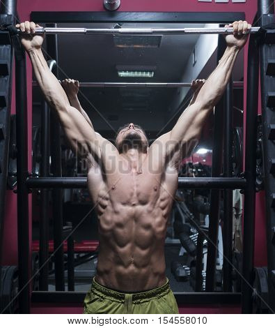 A young muscular man usng pull-down bar at the gym