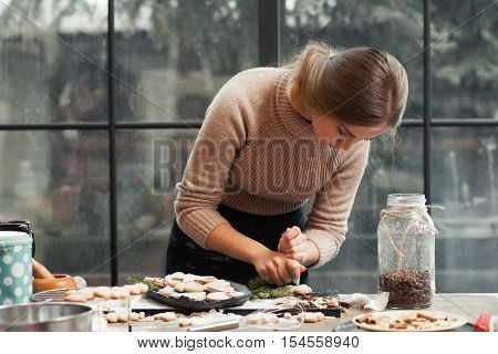 Young woman decorating pastry at kitchen. Young confectioner making Christmas colorful gingerbread cookies. Homemade bakery, xmas sweet, winter holidays concept