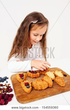 Little girl stuff cakes with fresh berries. Young lassie cooking sweet treat for family. Homemade bakery, children culinary, pastry making concept