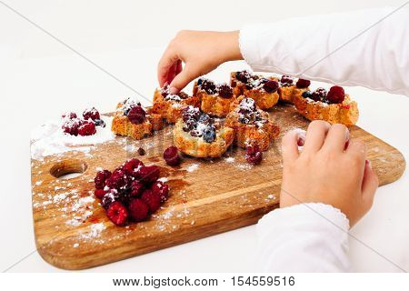 Kid decorating cakes with fresh berries, girl pov. Young confectioner cooking sweet treat at kitchen, white background. Homemade bakery, children culinary, pastry making concept