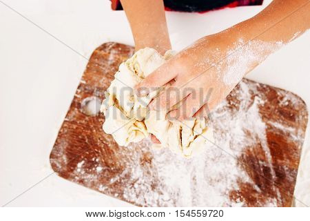 Kid hands with dough close-up. Top view on little baker kneading raw pastry above wooden cutting board. Homemade bakery, children culinary, sweets making concept