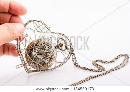 Pocket watch in a heart shaped metal wire cage in hand