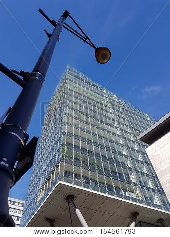 Street lamp. modern lamppost against modern building facade in daylight in Manchester UK