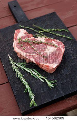 Rib eye steak and herbs on a black wooden board