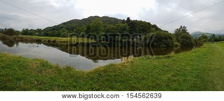 Panoramic view of pond and beautiful reflections in Ambleside countryside Cumbria UK