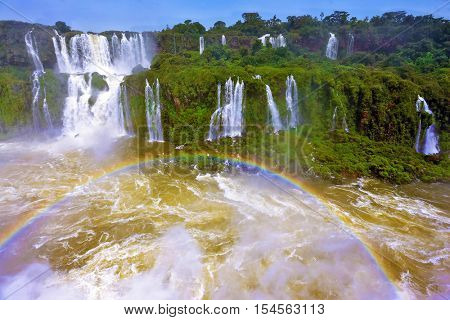 Fantastically spectacular boiling and thundering waterfalls of Iguazu. Waterfalls in Brazil.  Above the water is a picturesque rainbow