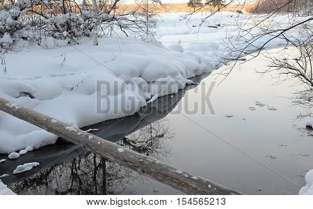 Fairy winter landscape with a stream and snowy shores