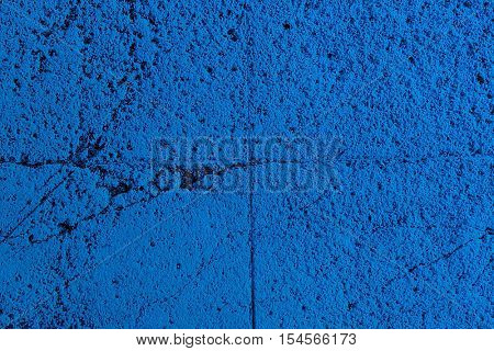 Background texture of a painted porous blue wall with a rough pitted surface and cracks in a full frame view
