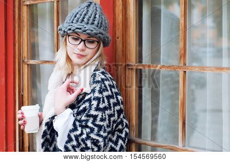 Student girl in autumn park wearing glasses warm cardigan and thick knitted hat drinking hot coffee in paper cup. Fall street style city look.