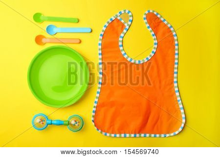 Bright baby tableware and bib on yellow background