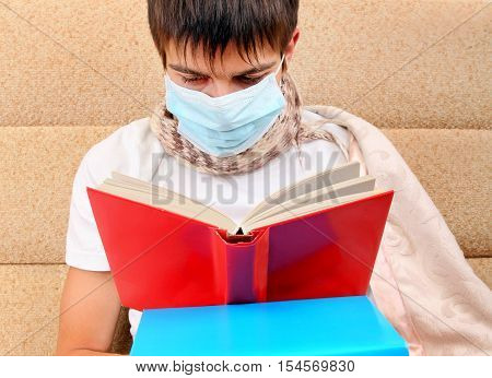 Sick Teenager in Flu Mask read a Book on the Sofa at the Home