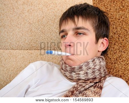 Sick Teenager with Thermometer on the Sofa at the Home