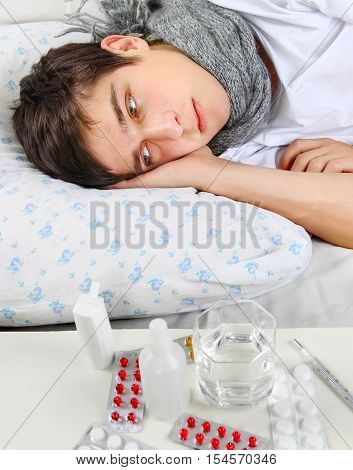 Sad and Sick Young Man on the Bed