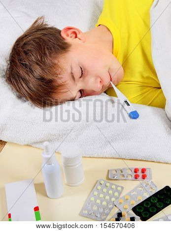 Sick Kid with Thermometer on the Bed