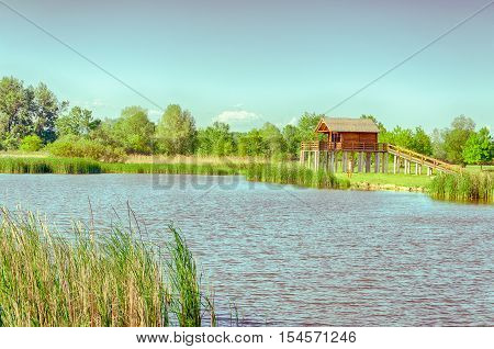vintage summer landscape. one of the backwaters of the Tisza (Tisa) river in Tiszalok, Hungary. yellow stilt house. hungarian countryside. clear blue sky and forest green.