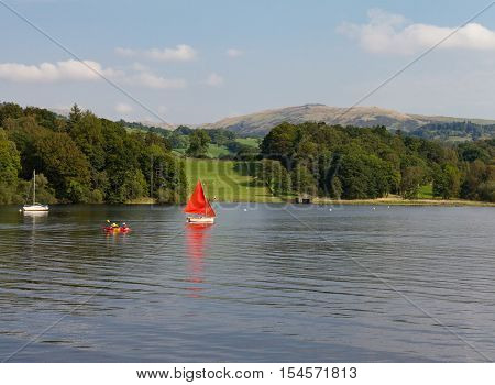 Sailboat Canoe and Sailboat n Lake Windermere Cumbria UK with the forest and mountains in the background