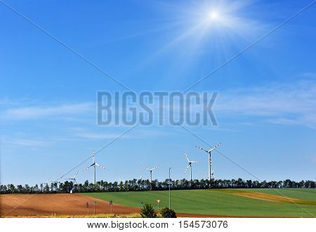 Wind turbines on blue sunshiny sky background