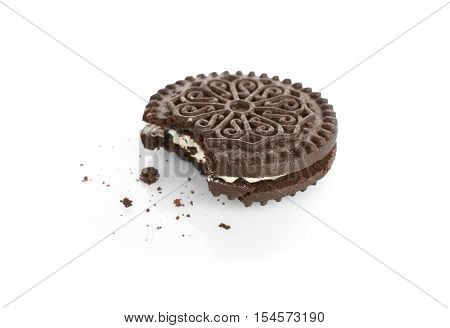 Bitten tasty cookie and crumbs on white background