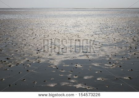 Sandy Ocean Floor on island Mando. Low water at the Danish Wadden Sea National Park with Koresand in the background.