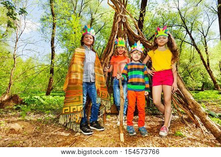 Four cute kids in Red Indian's costumes, standing next to wigwam, made of branches, at the park