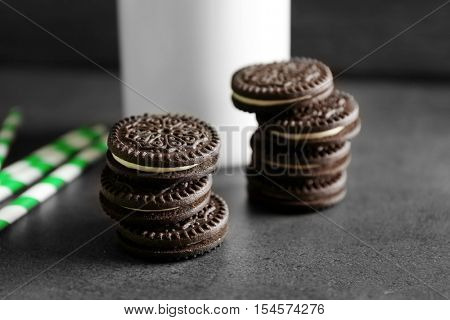 Chocolate cookies and straws on dark table, close up view
