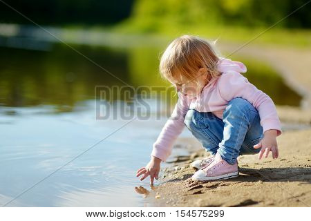 Adorable toddler girl playing by a river in autumn park on a beautiful sunny day