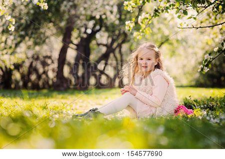 spring portrait of beautiful child girl walking outdoor in blooming garden
