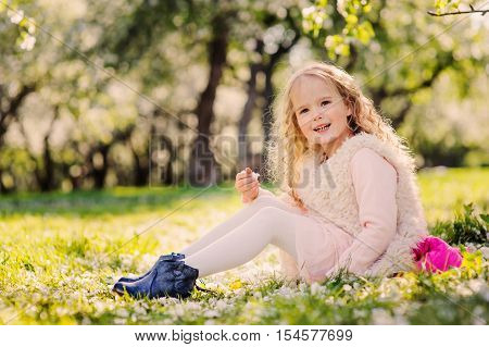 spring portrait of beautiful child girl walking outdoor in blooming garden