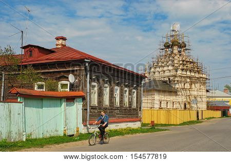 Girl rides a bicycle through ancient streets of ancient Russian city of Kolomna near wooden house and temple on restoration. Russia, Kolomna. May 7, 2011