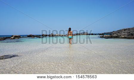transparent aquamarine blue green ocean sea turquoise water surrounded by rocky volcanic rocks stones in clear sunny weather in Greece, slender young woman is standing in the water, the view from the back looking out into the distance, flowing hair