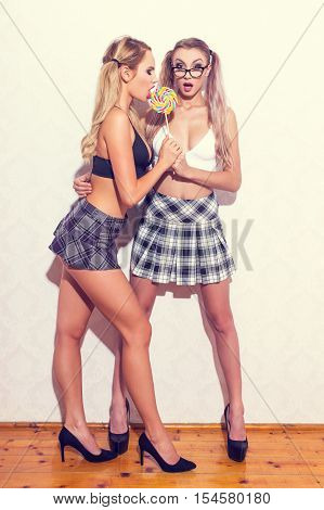 Sexy lesbian blonde women with lollipop posing at wall vintage